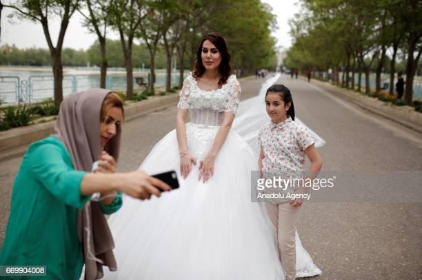 Iraqi people take photos with the Iranian model Chunur Muhammed as she displays the custom made 200 meter long wedding dress at Sami Abdulrahman Park...
