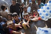 Iraqi people take water from a humanitarian aid convoy in Amerli on September 1 2014 after Iraqi forces broke through to the jihadistbesieged Shiite...
