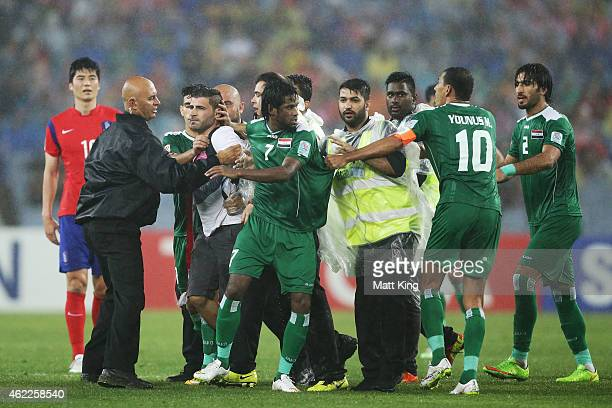 Iraqi players intervene as a pith invader is stopped by security staff during the Asian Cup Semi Final match between Korea Republic and Iraq at ANZ...