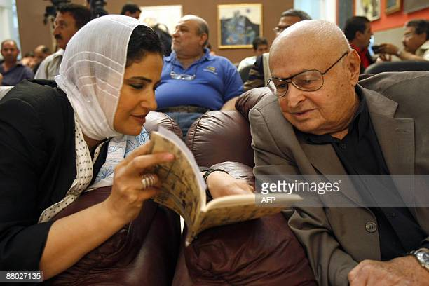 Iraqi poet Amal alJaburi speaks with former Iraqi football coach AmmoBaba who led the Iraqi soccer team for some 30 years during the finals of a...