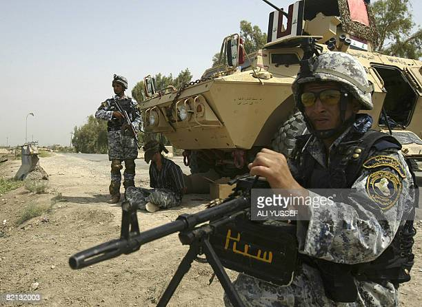 Iraqi police commandos stand guard near a blindfolded suspect in Baquba 60 kms north of Baghdad on July 31 2008 Iraqi forces backed by US troops...
