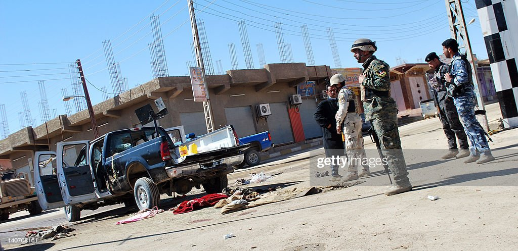 Iraqi police inspect the scene after policemen were slain in the western city of Haditha on March 5, 2012. Suspected Al-Qaeda gunmen, some wearing army uniforms, raged through this western Iraq city in a pre-dawn shooting spree that killed 27 policemen, including two officers killed execution-style.