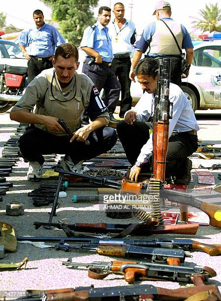 Iraqi police present 23 August 2003 confiscated weapons to the press after they conducted dawn raids on houses in the northwestern Baghdad suburb...