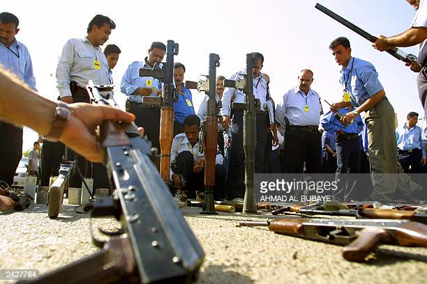 Iraqi police present 23 August 2003 confiscated weapons to the press after Iraqi police conducted dawn raids on houses in the northwestern Baghdad...