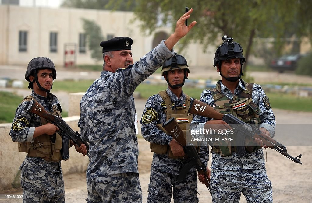 Iraqi policemen are seen on patrol inside a military base in Baghdad, on June 11, 2014, after the parliament had received a joint request from Iraqi Prime Minister Nuri al-Maliki and the president's office to declare a state of emergency -- the procedure laid down in the constitution. Jihadists seized in the city of Mosul, Iraq's second and Nineveh province on June 10, in a major blow to the government apparently unable to halt the progress of armed. AFP PHOTO/AHMAD AL-RUBAYE