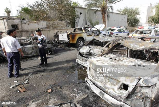 Iraqi policemen check the site of a blast which took place the previous day in the Iraqi capital Baghdad on April 29 2017 A car bomb attack on the...