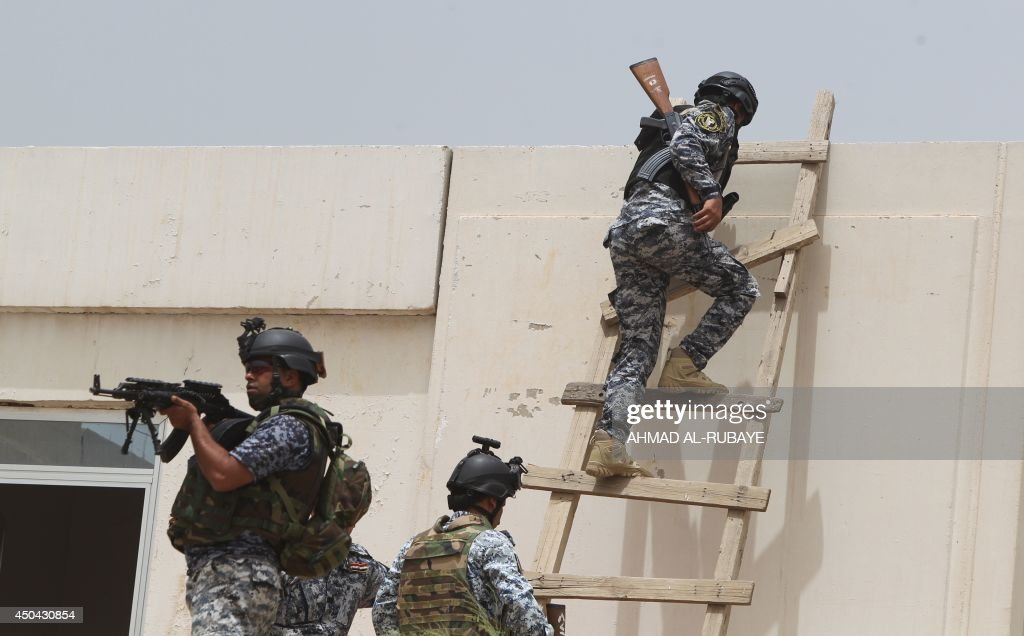Iraqi policemen climb onto a roof of a military base in Baghdad, on June 11, 2014, after the parliament had received a joint request from Iraqi Prime Minister Nuri al-Maliki and the president's office to declare a state of emergency -- the procedure laid down in the constitution. Jihadists seized in the city of Mosul, Iraq's second and Nineveh province on June 10, in a major blow to the government apparently unable to halt the progress of armed. AFP PHOTO/AHMAD AL-RUBAYE