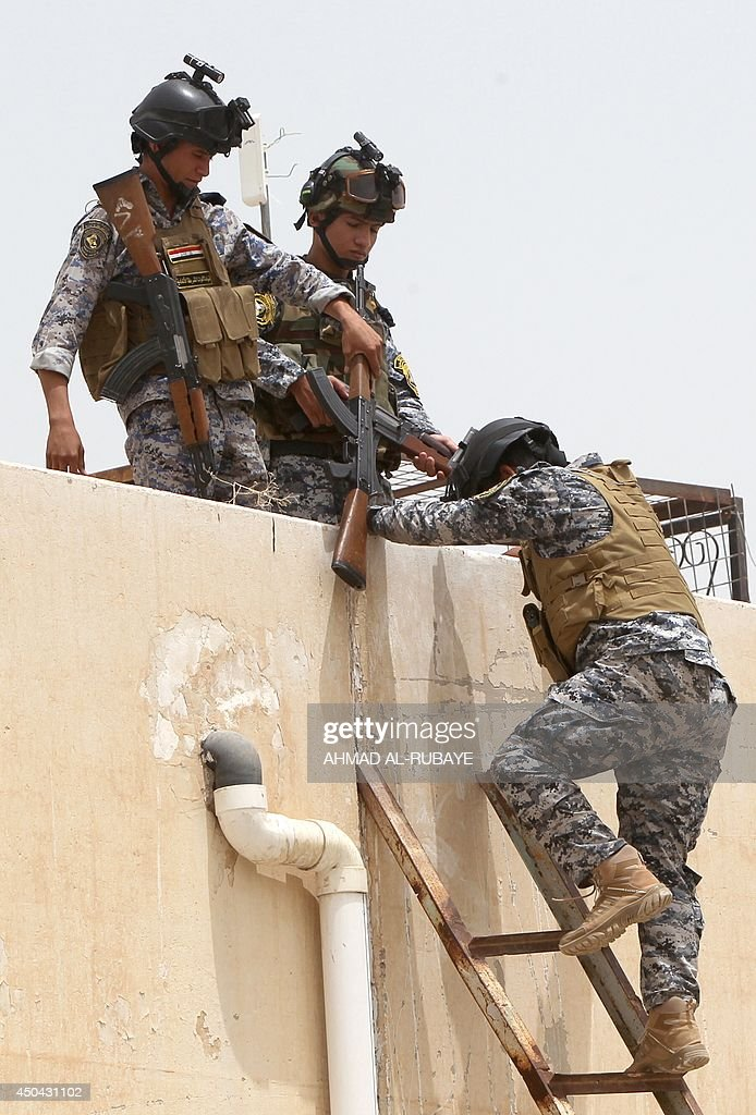 Iraqi policemen climb onto a roof of a military base in Baghdad, on June 11, 2014, after the parliament had received a joint request from Iraqi Prime Minister Nuri al-Maliki and the president's office to declare a state of emergency -- the procedure laid down in the constitution. Jihadists seized in the city of Mosul, Iraq's second and Nineveh province on June 10, in a major blow to the government apparently unable to halt the progress of armed.