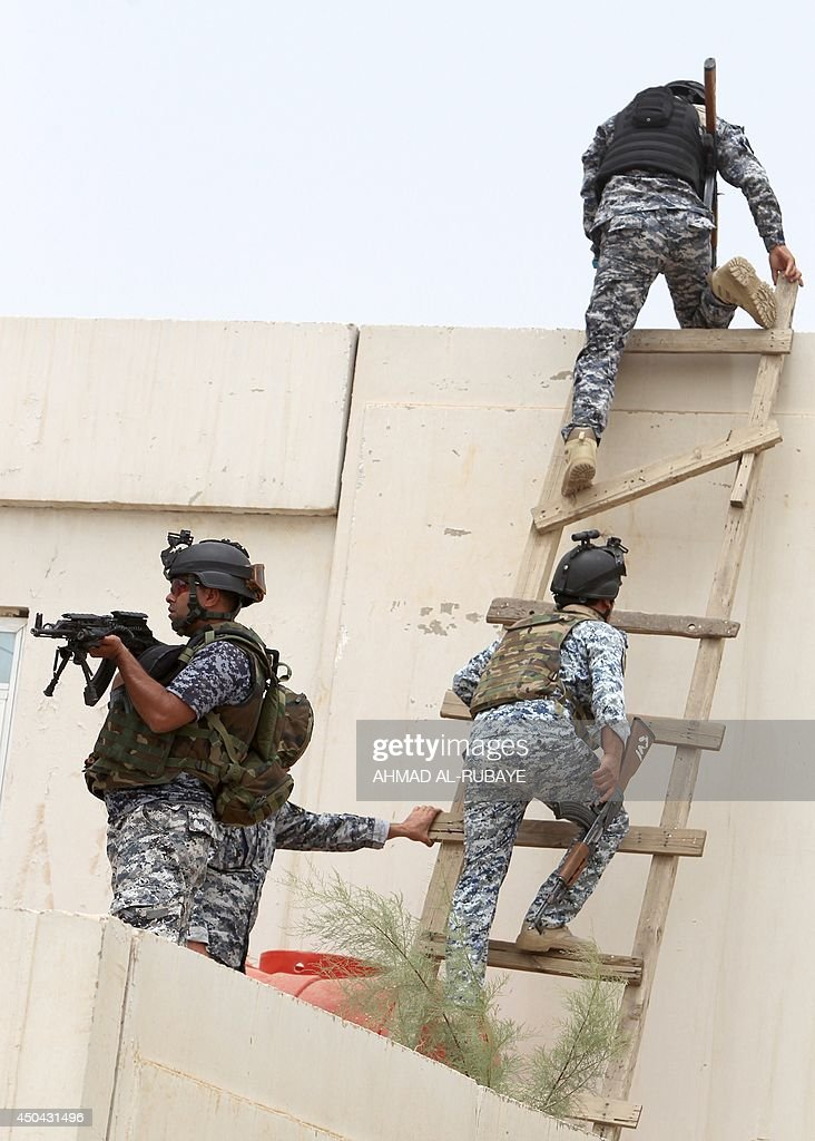 Iraqi policemen climb onto a roof of a military base in the capital Baghdad, on June 11, 2014, after the parliament had received a joint request from Iraqi Prime Minister Nuri al-Maliki and the president's office to declare a state of emergency -- the procedure laid down in the constitution. Jihadists seized in the city of Mosul, Iraq's second and Nineveh province on June 10, in a major blow to the government apparently unable to halt the progress of armed.