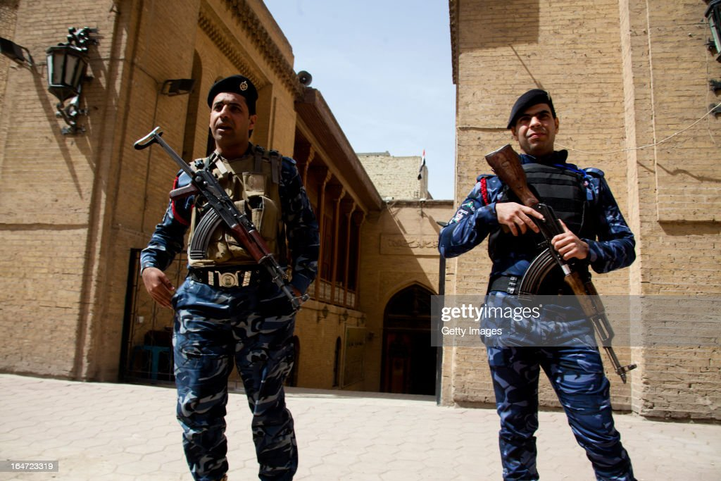 Iraqi policemen guard the entrance to the Baghdad Folklore Museum, March 18, 2013 in Baghdad, Iraq. Ten years after the regime of Saddam Hussein was toppled from power, Baghdad continues to show the scars of the war. In vast areas, infrastructure is fractured and basic services are lacking, however, some areas of the capital are showing promising signs of recovery.