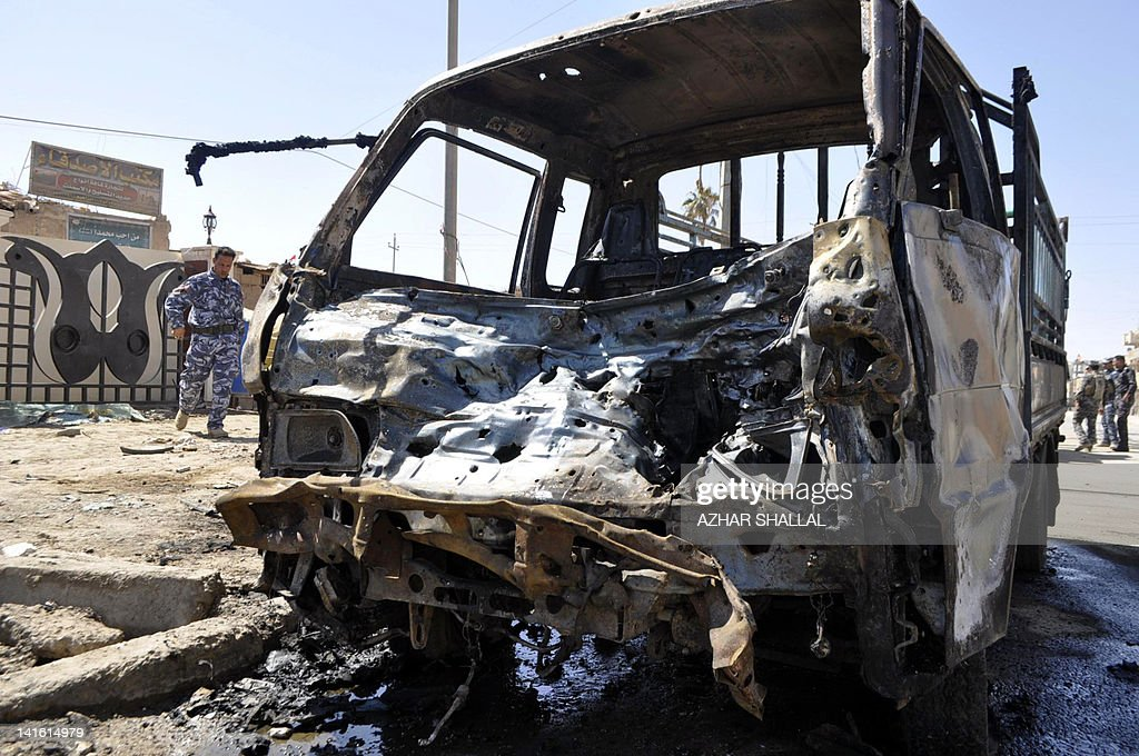 Iraqi policemen inspect the site of a car bomb in Ramadi, capital of western Anbar province, that killed two people and wounded 11, on March 20, 2012. A wave of attacks in a dozen Iraqi cities killed at least 44 people on the anniversary of the US-led invasion of the country, just days before Baghdad hosts a landmark Arab summit.