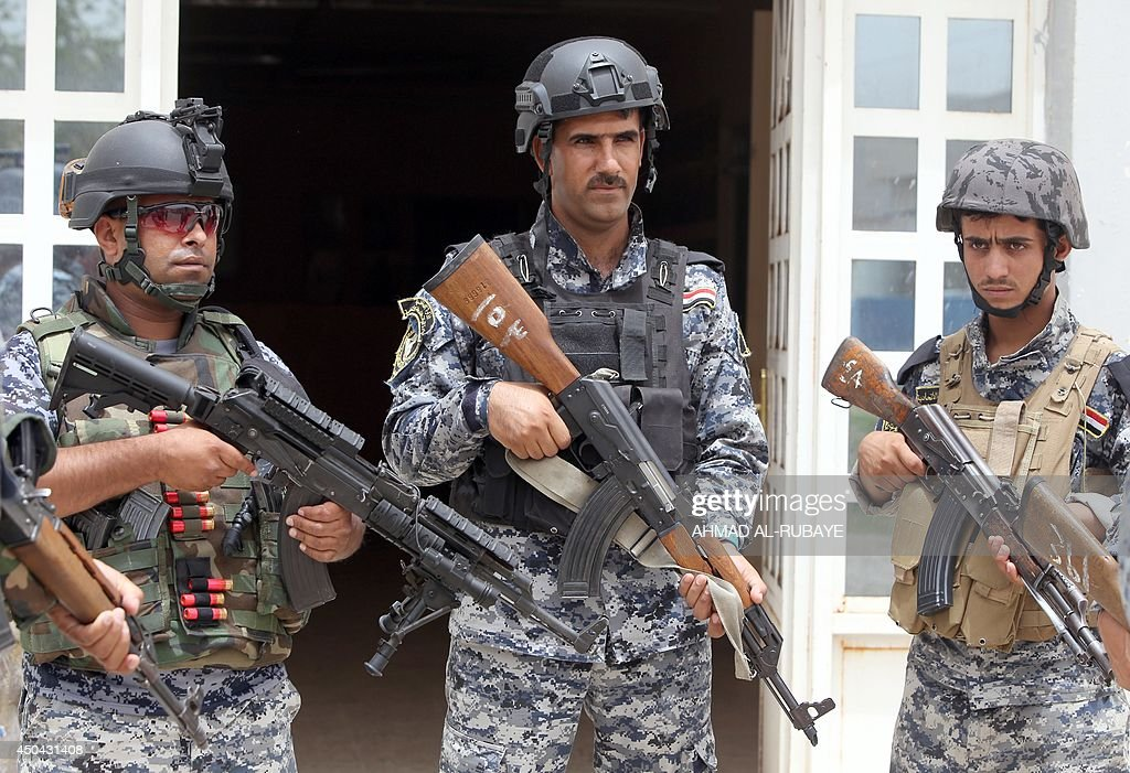 Iraqi policemen listen to a briefing inside a military base in the capital Baghdad, on June 11, 2014, after the parliament had received a joint request from Iraqi Prime Minister Nuri al-Maliki and the president's office to declare a state of emergency -- the procedure laid down in the constitution. Jihadists seized in the city of Mosul, Iraq's second and Nineveh province on June 10, in a major blow to the government apparently unable to halt the progress of armed.