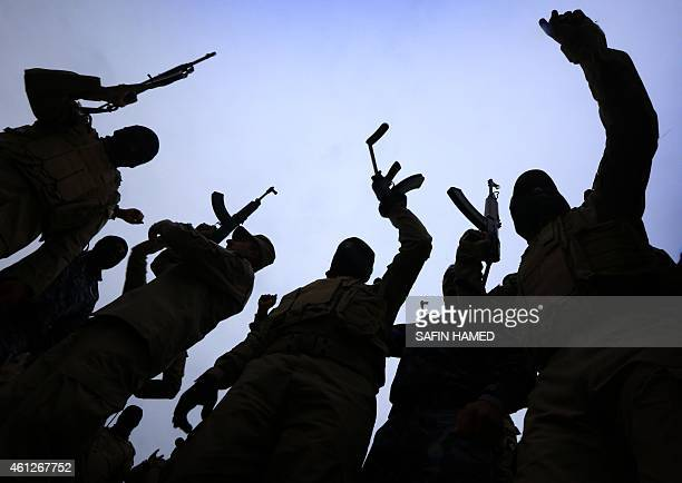 Iraqi policemen raise their weapons during a training session at a camp in the Bardarash district 30 kilometres northeast of Mosul on January 10 2015...
