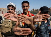Iraqi policemen show the palm of their hands with the word 'police' 'Street 60' and 'No to ISIL' written on them after the southern districts of the...