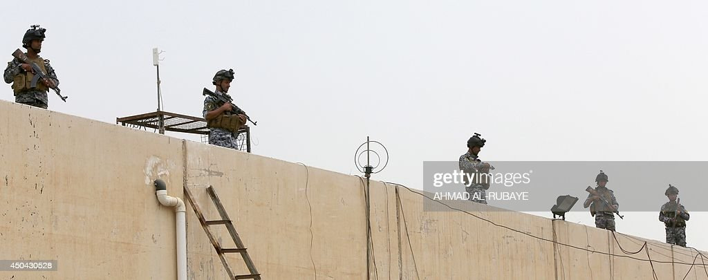 Iraqi policemen stand guard on a roof of a military base in Baghdad, on June 11, 2014, after the parliament had received a joint request from Iraqi Prime Minister Nuri al-Maliki and the president's office to declare a state of emergency -- the procedure laid down in the constitution. Jihadists seized in the city of Mosul, Iraq's second and Nineveh province on June 10, in a major blow to the government apparently unable to halt the progress of armed.