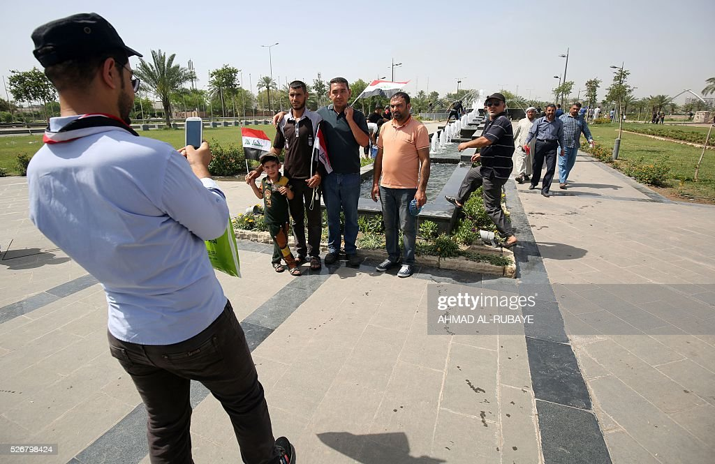 Iraqi pose for a photo in the parade grounds outside the parliament on May 1, 2016, the day after supporters of Shiite cleric Moqtada al-Sadr broke into Baghdad's heavily fortified 'Green Zone' after lawmakers again failed to approve new ministers. Thousands of wide-eyed Iraqis marvelled at the fountains, flowers and perfect lawns in the capital's Green Zone, a day after protesters breached the walls of the fortified area. The visitors were mostly protesters who broke in on Saturday but also included Baghdadis taking the opportunity to see an area that was off-limits for so many years that it acquired almost mythical status in the psyche of ordinary citizens. RUBAYE