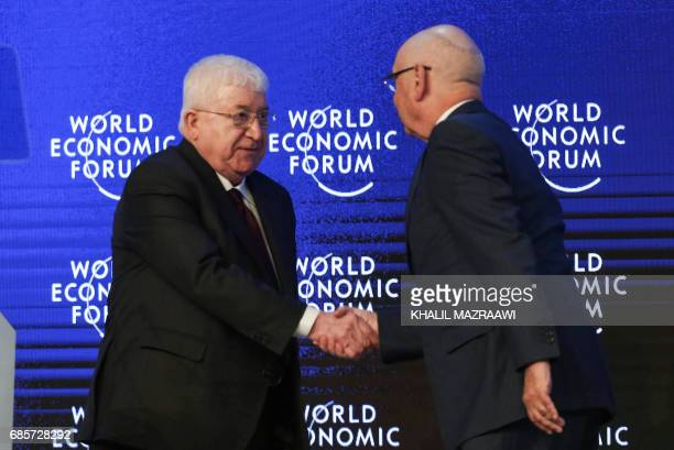 Iraqi President Fuad Masum shakes hands with Founder and Executive Chairperson of the World Economic Forum Klaus Schwab during the opening session of...