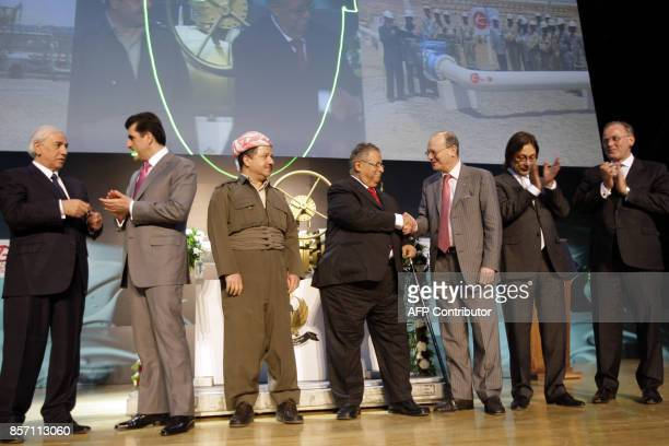 Iraqi President Jalal Talabani shakes hands with an executive from Turkey's Genel Enerji as they stand with officials from the Calgarybased Addax...