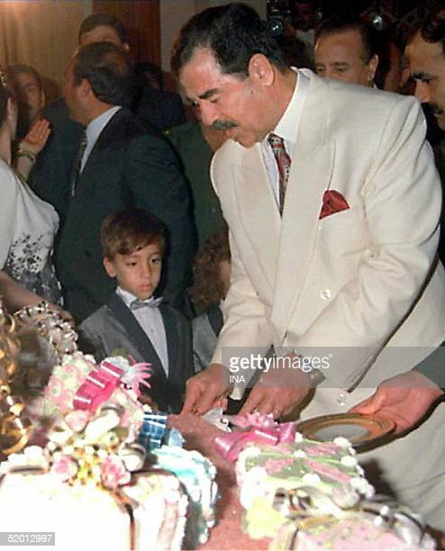 Iraqi President Saddam Hussein cuts his birthday cake 28 April in Tikrit Iraq marked the leader's 60th birthday with lavish celebrations and tributes