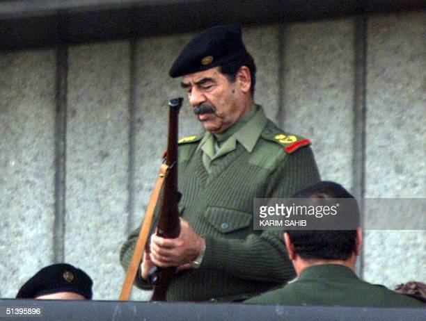 Iraqi President Saddam Hussein prepares his gun to give the signal for a military parade in Baghdad late 20 November 2000 Thousands of Iraqis marched...