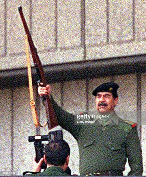 Iraqi president Saddam Hussein raises his rifle in a salute and fires it November 20 2000 durring Grand Day of Quds festivities in Baghdad Grand Day...