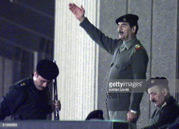 Iraqi President Saddam Hussein salutes the crowd during a military parade in Baghdad late 20 November 2000 Thousands of Iraqis marched through the...