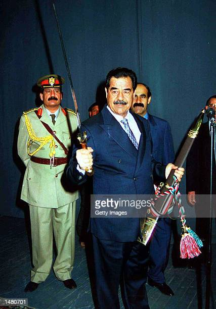 Iraqi President Saddam Hussein shows a sword given to him as a gift before being sworn in as president October 17 2002 in Baghdad Iraq Saddam Hussein...