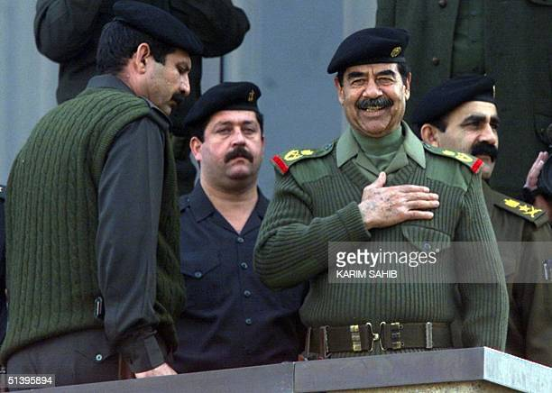 Iraqi President Saddam Hussein surrounded by body guards salutes the crowd during a military parade in Baghdad late 20 November 2000 Thousands of...