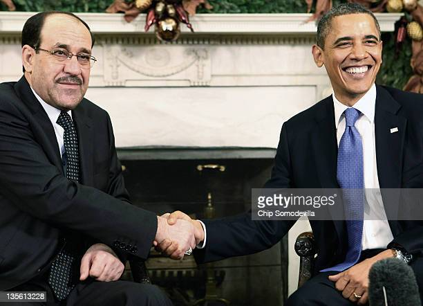 Iraqi Prime Minister Nouri AlMaliki shakes hands with US President Barack Obama in the Oval Office at the White House December 12 2011 in Washington...