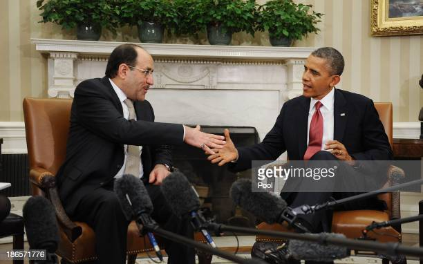 Iraqi Prime Minister Nouri AlMaliki shakes hands with US President Barack Obama in the Oval Office at the White House November 1 2013 in Washington...