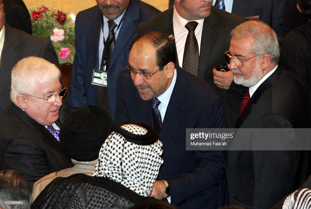 Iraqi Prime minister Nuri al-Maliki (C) shakes hands with Acting speaker, Fouad Massoum (L) and other lawmakers after the first Parliament session on June 14, 2010 at the Green Zone in Baghdad, Iraq. The Iraqi parliament convened for the first time since elections in March where former Prime Minister Iyad Allawi led Iraqiya, a cross sectarian alliance to the most seats but short of a majority to form government. Incumbent Prime Minister, Nuri al-Maliki is hoping to remain in power by forming a government with other Shi'ite parties, including followers of anti-American cleric Moqtada al-Sadr.