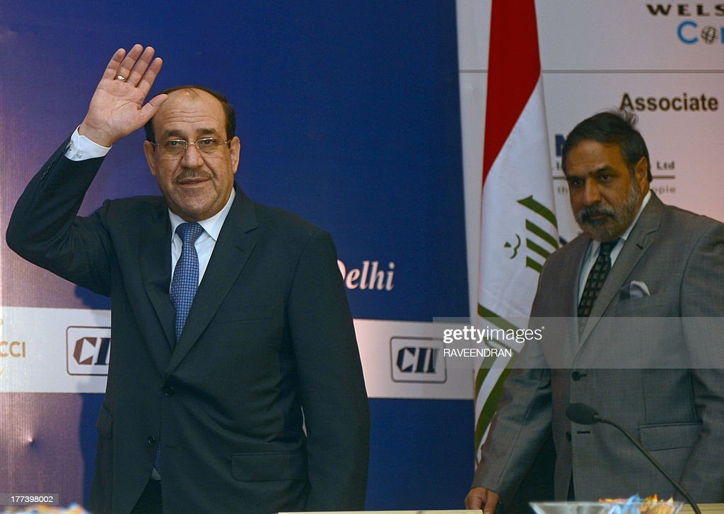 Iraqi Prime Minister Nuri al-Maliki (L) waves to delegates while Indian Minister for Commerce and Industry Anand Sharma (R) looks on during a business meeting in New Delhi on August 23, 2013. Iraqi Prime Minister Nuri al-Maliki is in India to push for investment in much-needed reconstruction, as New Delhi looks to secure critical energy supplies.