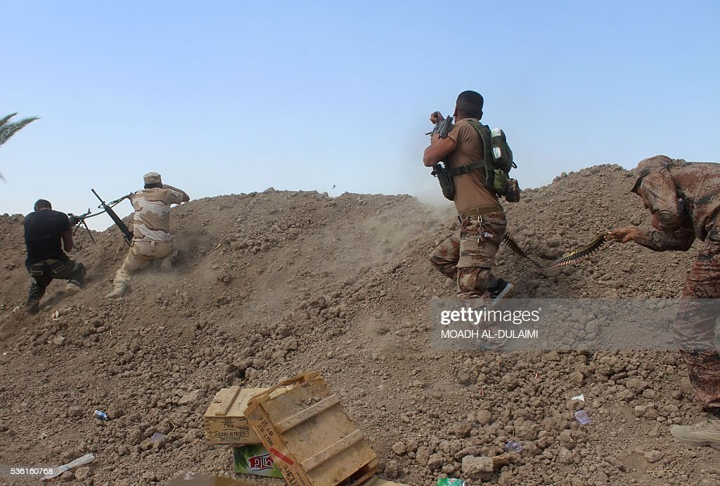 Iraqi pro-governement forces fire their weapons on a front line in the Albu Huwa area, south of Fallujah near the Euphrates river, on May 31, 2016, during an operation aimed at retaking areas from the Islamic State group. Iraqi forces launched an offensive a week ago to recapture Fallujah, which became an IS group stronghold after its fighters seized the city in January 2014. / AFP / MOADH