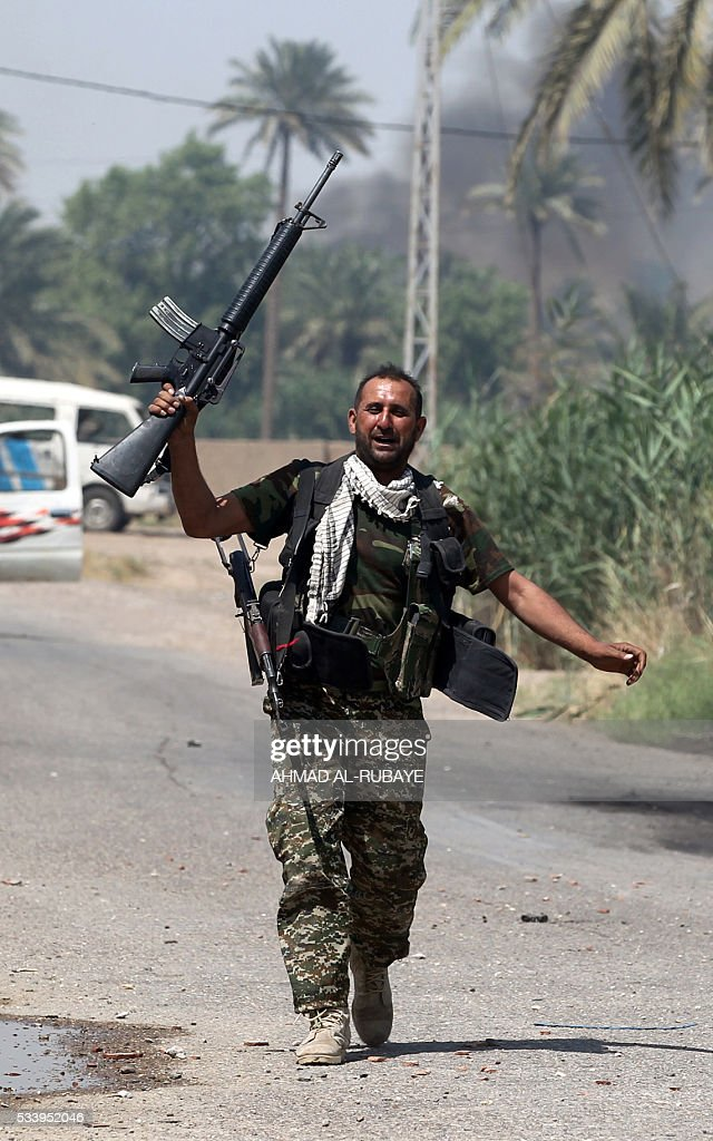 Iraqi pro-government fighter flashes his weapon as he takes part in an operation in al-Shahabi village, east of Fallujah, to retake the city from Islamic State (IS) group, on May 24, 2016. Iraqi forces cleared areas around Fallujah on May 24 after launching an assault to retake the city, tightening their siege on Islamic State group fighters. With the jihadists surrounded and outnumbered, the recapture of their iconic bastion looked ultimately inevitable, especially after IS suffered a string of losses in recent months. / AFP / AHMAD