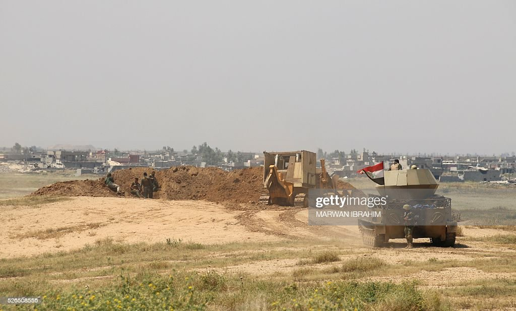 Iraqi pro-government forces and Shiite fighters from the Popular Mobilisation units hold position on April 30, 2016 as they launch an operation to retake the town of al-Bashir, south of the city of Kirkuk, from the Islamic State group (IS). The jihadist group (IS) fired rockets suspected of carrying a mustard agent last month from Bashir on Taza Khurmatu, another town in the northern province of Kirkuk where attack killed three children, wounded a large number of people and pushed thousands more to flee Taza out of fear that it would be repeated. IS overran large areas north and west of Baghdad in 2014, but has since lost significant ground to Iraqi forces backed by US-led air strikes and training. / AFP / Marwan IBRAHIM
