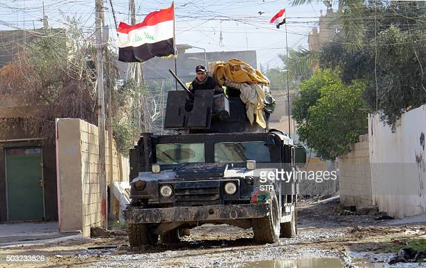 Iraqi progovernment forces drive a military vehicle during battles with Islamic State group jihadists as they try to secure all the neighbourhoods of...