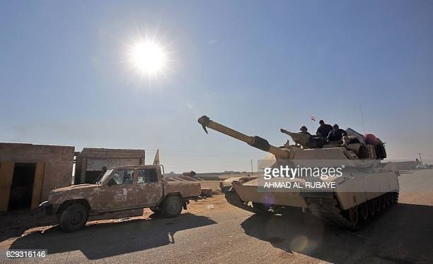 Iraqi progovernment forces drive a tank on December 12 2016 in the town of Tal Abtah south of Tal Afar during their assault to eject Islamic State...