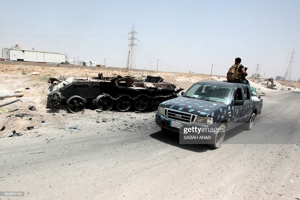 Iraqi pro-government forces drive past a destroyed tank in an area between the village of al-Sejar and Fallujah, on May 28, 2016, as they take part in a major assault to retake the city of Fallujah, from the Islamic State (IS) group. Hundreds of people fled the Fallujah area with the help of Iraqi forces who are fighting to retake the city from the Islamic State jihadist group, officials said. Iraqi forces launched an operation to recapture Fallujah, an IS stronghold located just 50 kilometres (30 miles) west of Baghdad, at the start of this week. / AFP / SABAH