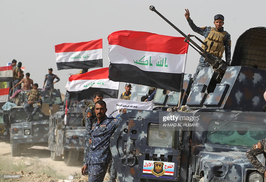 Iraqi pro-government forces gather in al-Shahabi village, east of the city of Fallujah, on May 24, 2016, as part of a major assault to retake the city from Islamic State (IS) group. Iraqi forces cleared areas around Fallujah on May 24 after launching an assault to retake the city, tightening their siege on Islamic State group fighters. With the jihadists surrounded and outnumbered, the recapture of their iconic bastion looked ultimately inevitable, especially after IS suffered a string of losses in recent months. / AFP / AHMAD