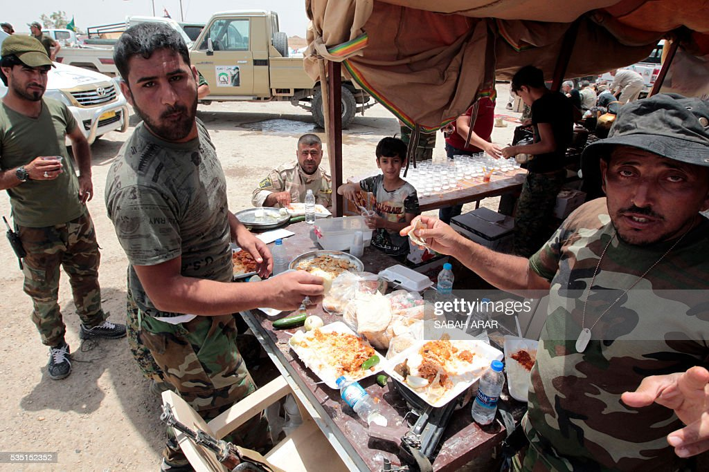 Iraqi pro-government forces have a meal in an area between the village of al-Sejar and Fallujah, on May 28, 2016, as they take part in a major assault to retake the city of Fallujah, from the Islamic State (IS) group. Hundreds of people fled the Fallujah area with the help of Iraqi forces who are fighting to retake the city from the Islamic State jihadist group, officials said. Iraqi forces launched an operation to recapture Fallujah, an IS stronghold located just 50 kilometres (30 miles) west of Baghdad, at the start of this week. / AFP / SABAH