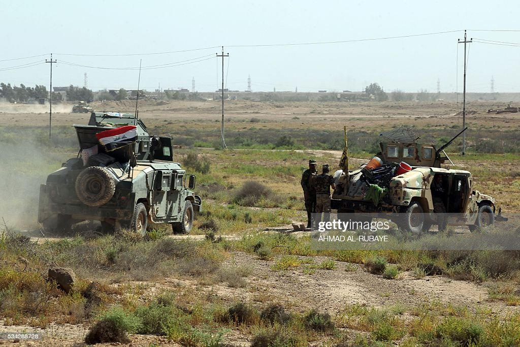 Iraqi pro-government forces hold a position near al-Sejar village, north-east of Fallujah, on May 25, 2016, as they take part in a major assault to retake the city from the Islamic State (IS) group. Iraqi forces, consisting of special forces, soldiers, police, paramilitary-fighters and pro-government tribesmen, launched a major assault to retake Fallujah, the scene of deadly battles during the US occupation and one of the toughest targets yet in Baghdad's war on the Islamic State group. / AFP / AHMAD