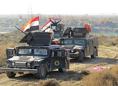 Iraqi progovernment forces hold their national flags on armored vehicles as they take position in alAramil area south of the Anbar province's capital...