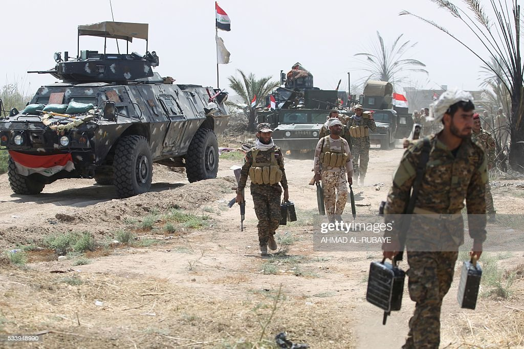 Iraqi pro-government forces stand gather in al-Shahabi village, east of Fallujah, on May 24, 2016, as part of a major assault to retake the city from Islamic State (IS) group. Iraqi forces cleared areas around Fallujah on May 24 after launching an assault to retake the city, tightening their siege on Islamic State group fighters. With the jihadists surrounded and outnumbered, the recapture of their iconic bastion looked ultimately inevitable, especially after IS suffered a string of losses in recent months. / AFP / AHMAD