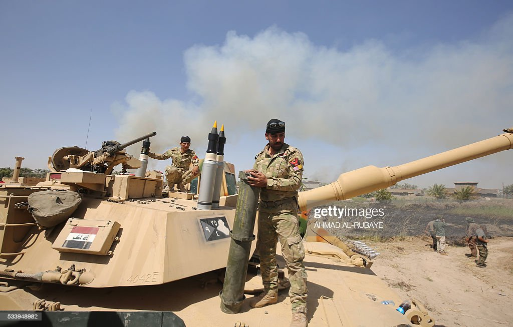 Iraqi pro-government forces stand on top of a tank in al-Shahabi village, east of Fallujah, on May 24, 2016, as part of a major assault to retake the city from Islamic State (IS) group. Iraqi forces cleared areas around Fallujah on May 24 after launching an assault to retake the city, tightening their siege on Islamic State group fighters. With the jihadists surrounded and outnumbered, the recapture of their iconic bastion looked ultimately inevitable, especially after IS suffered a string of losses in recent months. / AFP / AHMAD