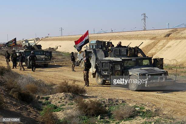 Iraqi progovernment forces take position in alAramil area south of the Anbar province's capital Ramadi during military operations on December 22 2015...