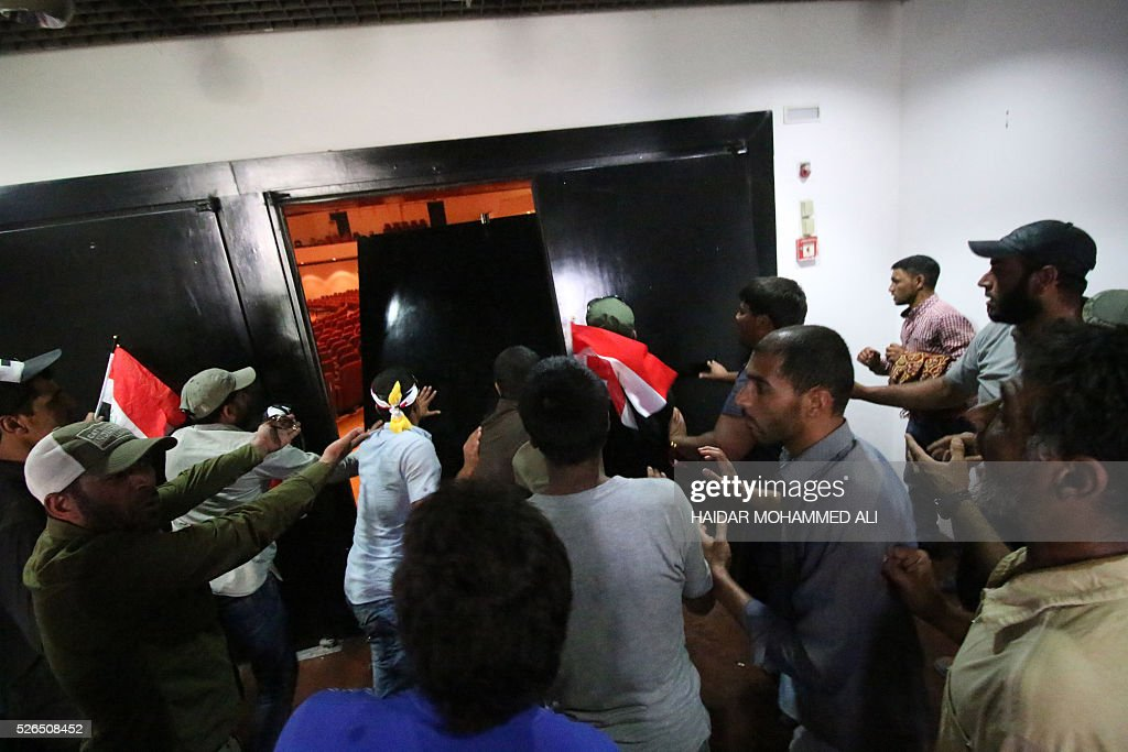 Iraqi protesters break down a door inside the parliament after entering Baghdad's heavily fortified 'Green Zone' on April 30, 2016. A protest held outside the Green Zone escalated after parliament again failed to reach a quorum and approve new ministers to replace the current government of party-affiliated ministers. / AFP / HAIDAR