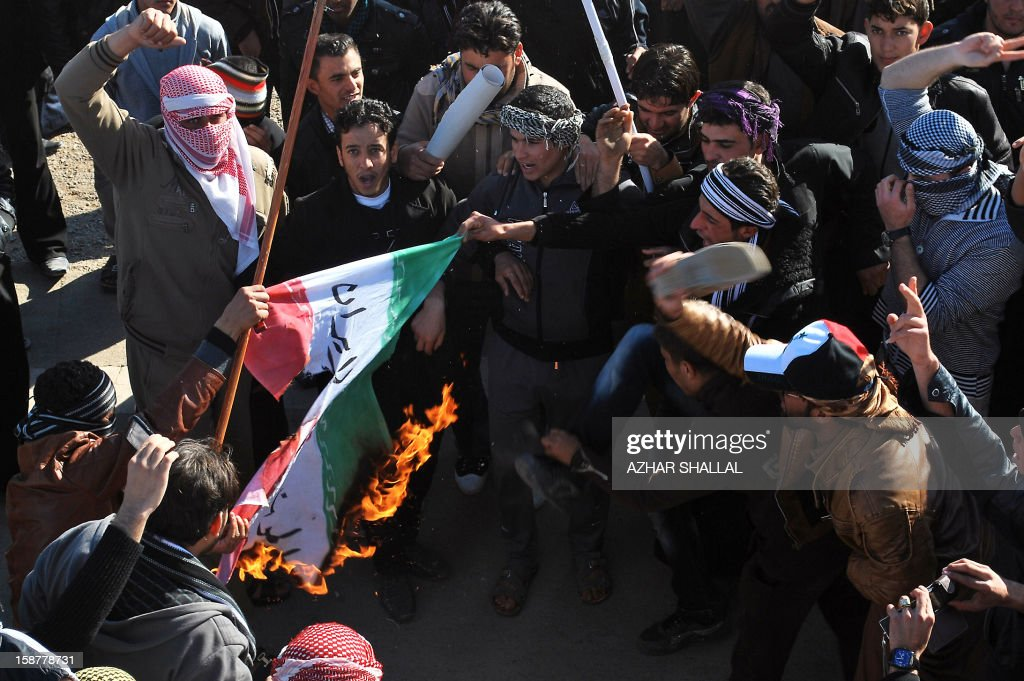 Iraqi protesters burn an Iranian flag reading 'Death to Iran' during a demonstration calling for the release of prisoners they allege were arrested on sectarian grounds by Iraq's Shiite-led authorities in Anbar's provincial capital Ramadi on December 28, 2012. The protesters opposed to Iraq's Prime Minister Nuri al-Maliki also blocked the main highway to Syria and Jordan for the sixth consecutive day, a move the premier slammed as 'unacceptable.'