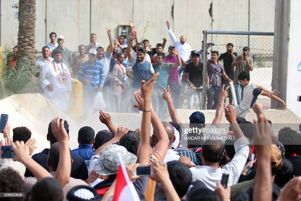Iraqi protesters celebrate as they open a breach in a concrete wall surrounding the parliament after breaking into Baghdad's heavily fortified 'Green Zone' on April 30, 2016. Thousands of angry protesters broke into Baghdad's Green Zone and stormed the parliament building after lawmakers again failed to approve new ministers. Jubilant supporters of cleric Moqtada al-Sadr invaded the main session hall, shouting slogans glorifying their leader and claiming that they had rooted out corruption. / AFP / HAIDAR