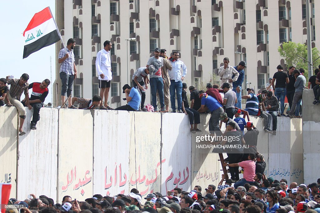 Iraqi protesters climb over a concrete wall surrounding the parliament (unseen) after breaking into Baghdad's heavily fortified 'Green Zone' on April 30, 2016. Thousands of angry protesters broke into Baghdad's Green Zone and stormed the parliament building after lawmakers again failed to approve new ministers. Jubilant supporters of cleric Moqtada al-Sadr invaded the main session hall, shouting slogans glorifying their leader and claiming that they had rooted out corruption. / AFP / HAIDAR