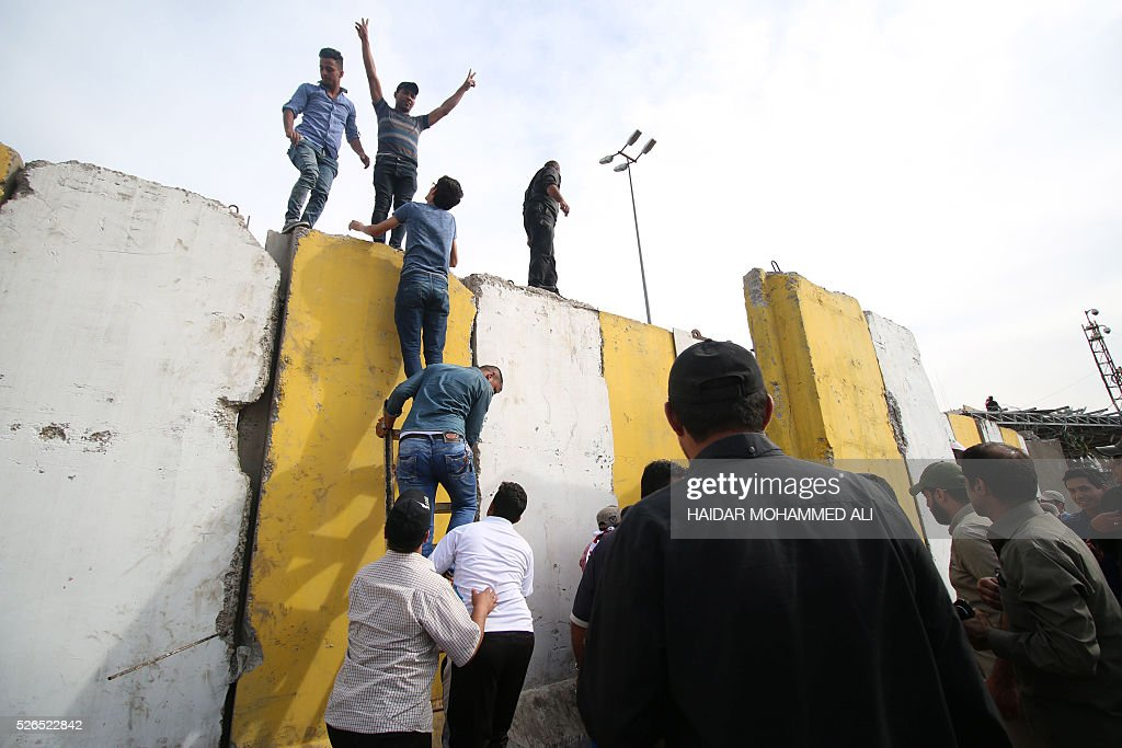 Iraqi protesters climb over a concrete wall surrounding the parliament after breaking into Baghdad's heavily fortified 'Green Zone' on April 30, 2016. Thousands of angry protesters broke into Baghdad's Green Zone and stormed the parliament building after lawmakers again failed to approve new ministers. Jubilant supporters of cleric Moqtada al-Sadr invaded the main session hall, shouting slogans glorifying their leader and claiming that they had rooted out corruption. / AFP / HAIDAR